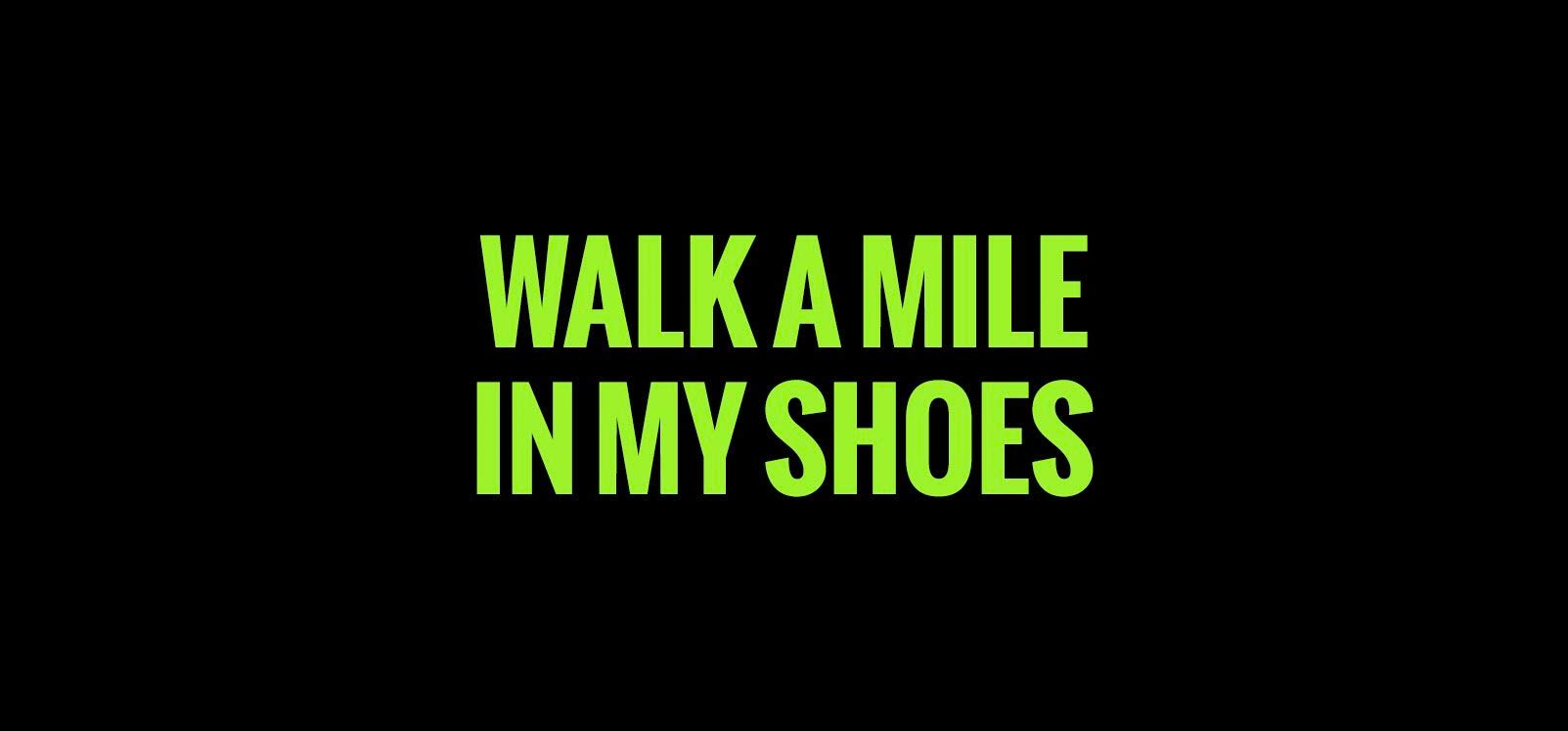 """""""Walk a mile in my shoes"""" written in green on black background"""